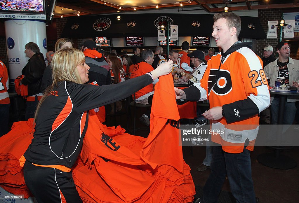 A Philadelphia Flyers fan is handed a t-shirt as he enters the arena prior to playing the Pittsburgh Penguins on January 19, 2013 at the Wells Fargo Center in Philadelphia, Pennsylvania.