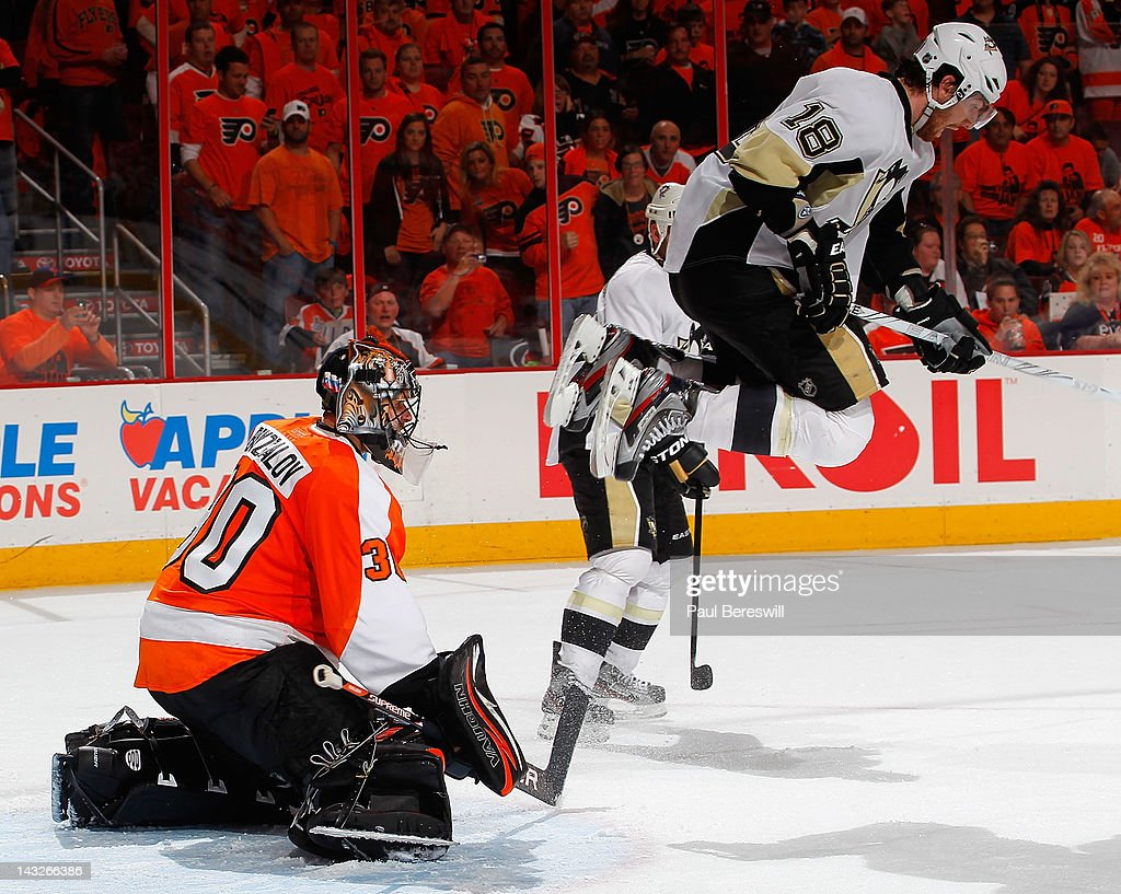 Philadelphia Flyers goalie Ilya Bryzgalov #30 plays the shot as James Neal #18 of the Pittsburgh Penguins leaps to avoid it in the third period of Game Six of the Eastern Conference Quarterfinals during the 2012 NHL Stanley Cup Playoffs at Wells Fargo Center on April 22, 2012 in Philadelphia, Pennsylvania. Flyers won 5-1 to eliminate the Penguins from the playoffs