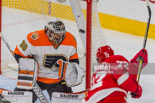 Philadelphia Flyers goalie Michal Neuvirth lets Detroit Red Wings center Andreas Athanasiou's shot slip by during the game between the Detroit Red...