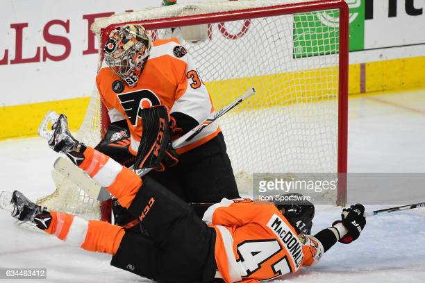 Philadelphia Flyers Goalie Steve Mason makes a save in front of a sliding Philadelphia Flyers Defenceman Andrew MacDonald during a National Hockey...