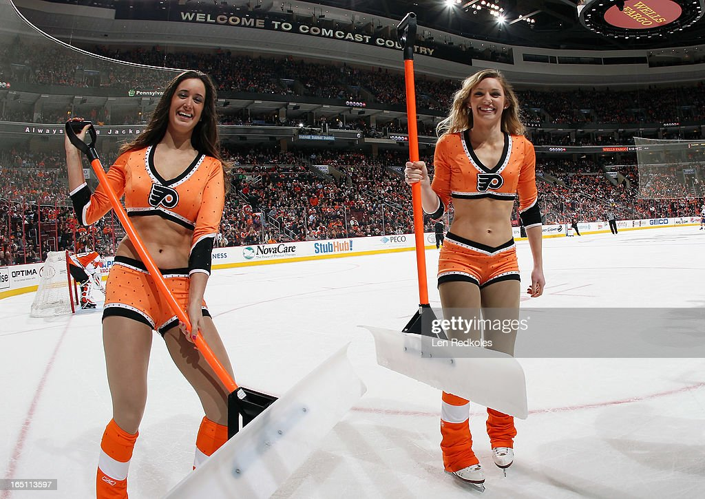 Philadelphia Flyers ice girls Amanda White(left) and Cassandra Latsios (right) skate off the ice after a stoppage in play against the New York Islanders on March 28, 2013 at the Wells Fargo Center in Philadelphia, Pennsylvania. The Islanders would go on to defeat the Flyers 4-3 in a shootout.