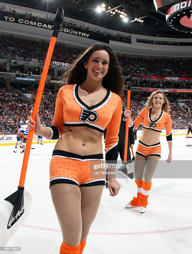 Philadelphia Flyers ice girls Amanda White (left) and Cassandra Latsios (right) skate off the ice after a stoppage in play against the New York Islanders on March 28, 2013 at the Wells Fargo Center in Philadelphia, Pennsylvania. The Islanders would go on to defeat the Flyers 4-3 in a shootout.