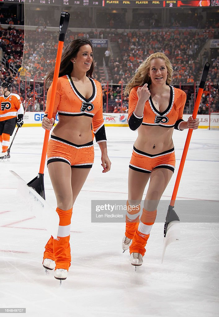 Philadelphia Flyers ice girls Amanda White (L) and Kimberly Webb skate off the ice after a stoppage in play against the New York Islanders on March 28, 2013 at the Wells Fargo Center in Philadelphia, Pennsylvania. The Islanders would go on to defeat the Flyers 4-3 in a shootout.