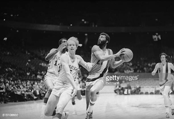Baltimore Bullets' Archie Clark has his eye on the basket after he steps ahead of 76'ers Tom Van Ardsdale and Leroy Ellis to score in the first...