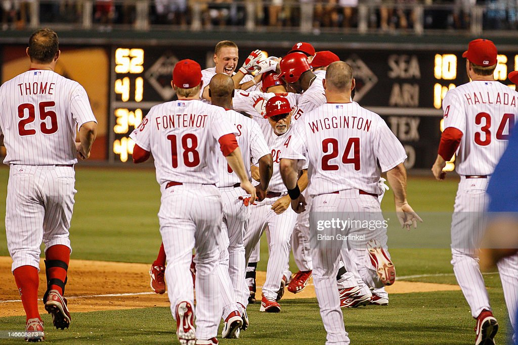 Philadelphia Phillies celebrate at first base around <a gi-track='captionPersonalityLinkClicked' href=/galleries/search?phrase=Placido+Polanco&family=editorial&specificpeople=213170 ng-click='$event.stopPropagation()'>Placido Polanco</a> #27 of the Philadelphia Phillies who was safe on first on an error to allow the game winning run in the bottom of the ninth inning of the game against the Colorado Rockies at Citizens Bank Park on June 20, 2012 in Philadelphia, Pennsylvania. The Phillies won 7-6.