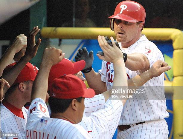 Philadelphia Phillies' Jeremy Giambi hifives his teammates in the dugout after his tworun homer in the first inning against the Milwaukee Brewers 15...