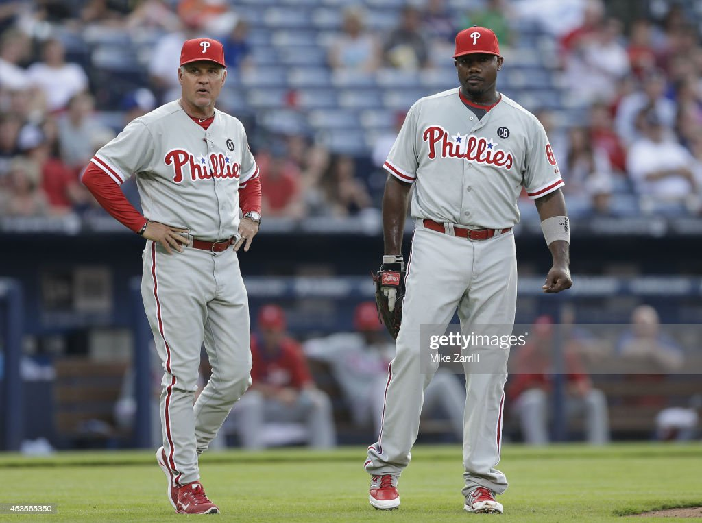 Philadelphia Phillies manager Ryne Sandberg #23 and first baseman Ryan Howard #6 of the Philadelphia Phillies watch the umpires as they discuss a call during the game against the Atlanta Braves at Turner Field on June 16, 2014 in Atlanta, Georgia.