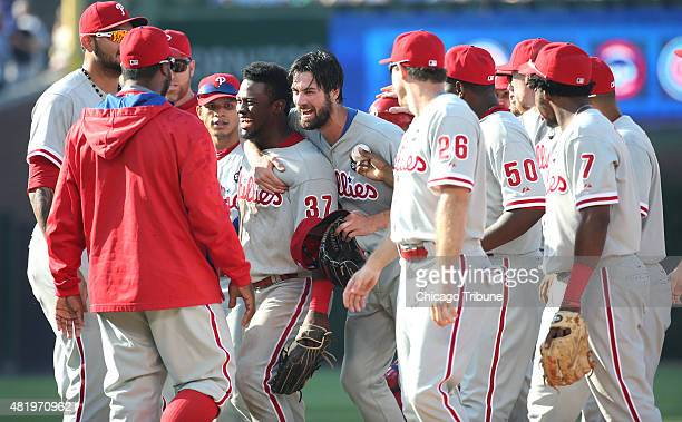 Philadelphia Phillies pitcher Cole Hamels center hugs center fielder Odubel Herrera after Herrera made a diving catch on the warning track to secure...