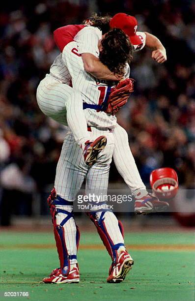 PHILADELPHIA PA OCTOBER 14 Philadelphia Phillies relief pitcher Mitch Williams jumps in the arms of catcher Darren Daulton air after striking out the...