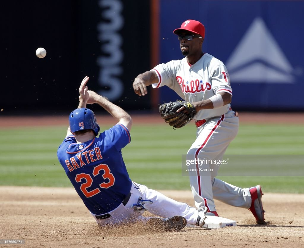 Philadelphia Phillies shortstop <a gi-track='captionPersonalityLinkClicked' href=/galleries/search?phrase=Jimmy+Rollins&family=editorial&specificpeople=204478 ng-click='$event.stopPropagation()'>Jimmy Rollins</a> #11 turns a double play on New York Mets right fielder Mike Baxter #23 in the third inning at Citi Field on April 27, 2013 in the Flushing neighborhood of the Queens borough of New York City. (Photo by Jason Szenes/Getty Images