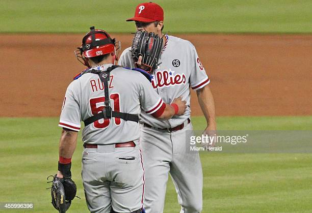 Philadelphia Phillies starting pitcher Cole Hamels talks to Phillies catcher Carlos Ruiz during the second inning of their game against the Miami...