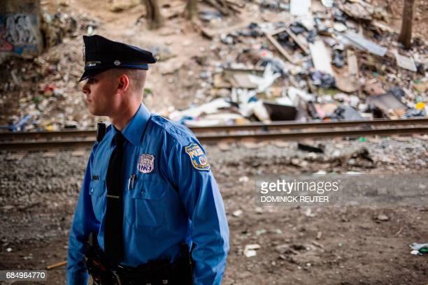 A Philadelphia Police officer patrols under a bridge near a heroin encampment in the Kensington neighborhood of Philadelphia Pennsylvania on April 14...