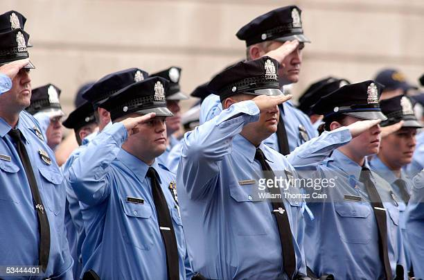 Philadelphia police officers salute as pallbearers carry the casket of Philadelphia Police Officer Gennaro Pellegrini Jr to St Anne's Church for a...