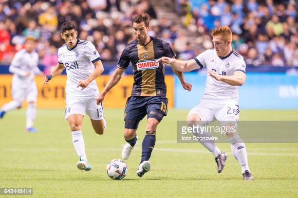 Philadelphia Union forward Chris Pontius kicks the ball ahead of defender Tim Parker and Vancouver Whitecaps midfielder Matias Laba during the game...