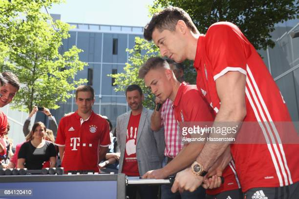 Philiip Lahm Joshua Kimmich and Robert Lewandowski of FC Bayern Muenchen play a fun table top football match at Paulaner headquarter Munich on May 17...