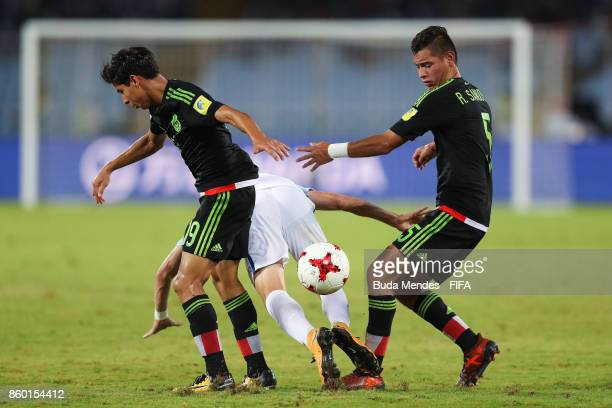 Philip Foden of England battles for the ball with Diego Lainez and Raul Sandoval of Mexico during the FIFA U17 World Cup India 2017 group F match...