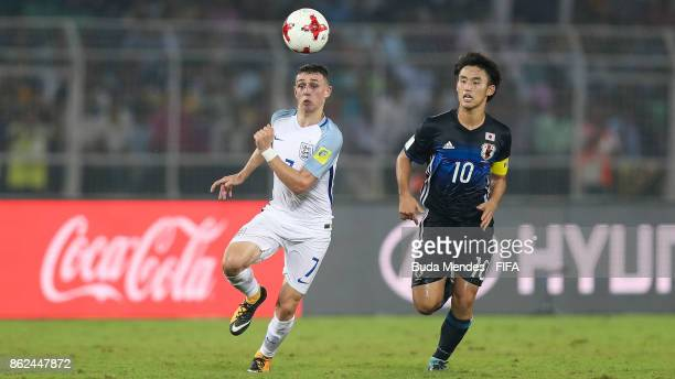 Philip Foden of England battles for the ball with Shimpei Fukuoka of Japan during the FIFA U17 World Cup India 2017 Round of 16 match between England...