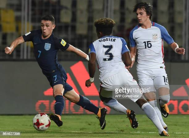 Philip Foden of England dribbles past Chris Gloster and Taylor Booth of USA during the quarterfinal football match between USA and England in the...