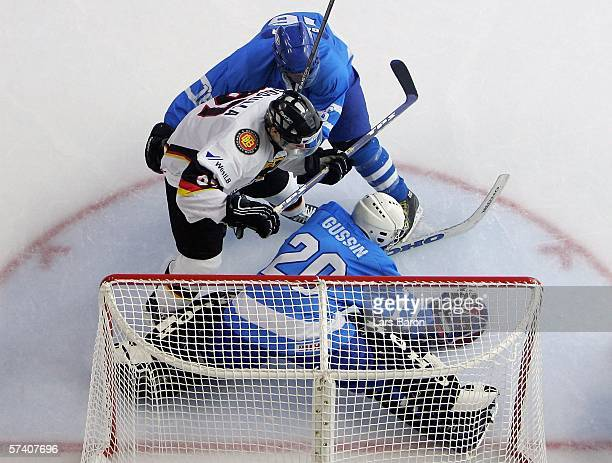 Philip Gogulla of Germany is stopped by goalie Jevgeny Gusin and Avishai Geller of Israel during the IIHF World Championship Division 1 Group A match...