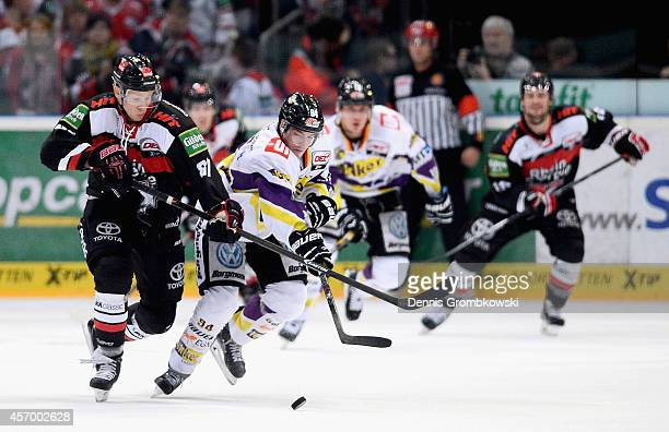 Philip Gogulla of Koelner Haie and Kyle Sonnenburg of Krefeld Pinguine battle for the puck during the DEL Ice Hockey match between Koelner Haie and...