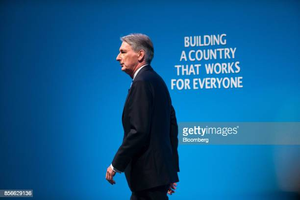 Philip Hammond UK chancellor of the exchequer arrives on stage to deliver his speech at the annual Conservative Party conference in Manchester UK on...