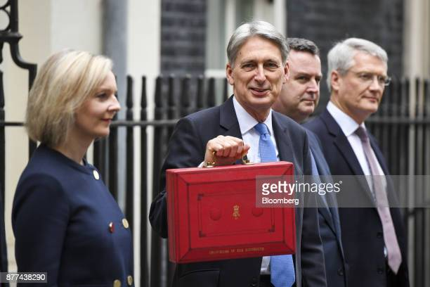 Philip Hammond UK chancellor of the exchequer center holds the dispatch box containing the budget as he poses for photographs with left to right Liz...