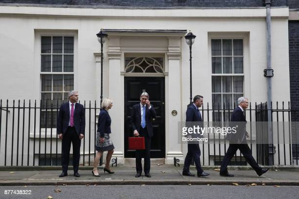 Philip Hammond UK chancellor of the exchequer center holds the dispatch box containing the budget as he poses for photographs with left to right...