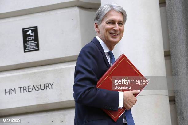 Philip Hammond UK chancellor of the exchequer holds a document folder as he arrives at the treasury offices in London UK on Tuesday Oct 17 2017 UK...