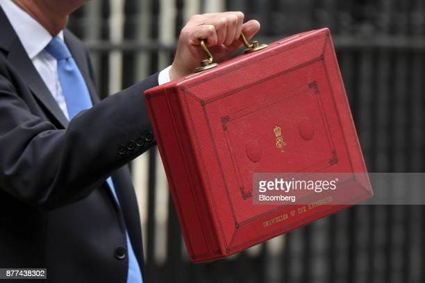 Philip Hammond UK chancellor of the exchequer holds the dispatch box containing the budget outside 11 Downing Street before presenting an annual...
