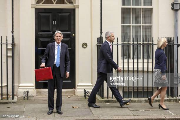 Philip Hammond UK chancellor of the exchequer left holds the dispatch box containing the budget as he poses for photographs while Stephen Barclay...