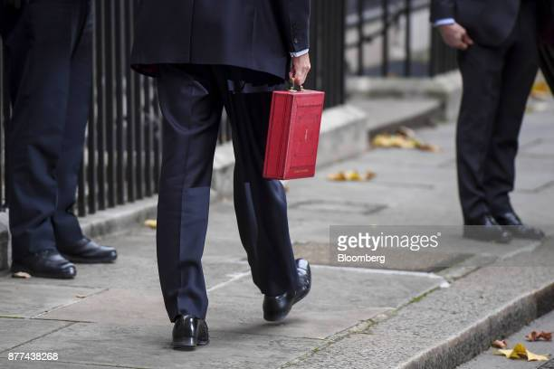 Philip Hammond UK chancellor of the exchequer walks to his car while holding the dispatch box containing the budget outside 11 Downing Street before...