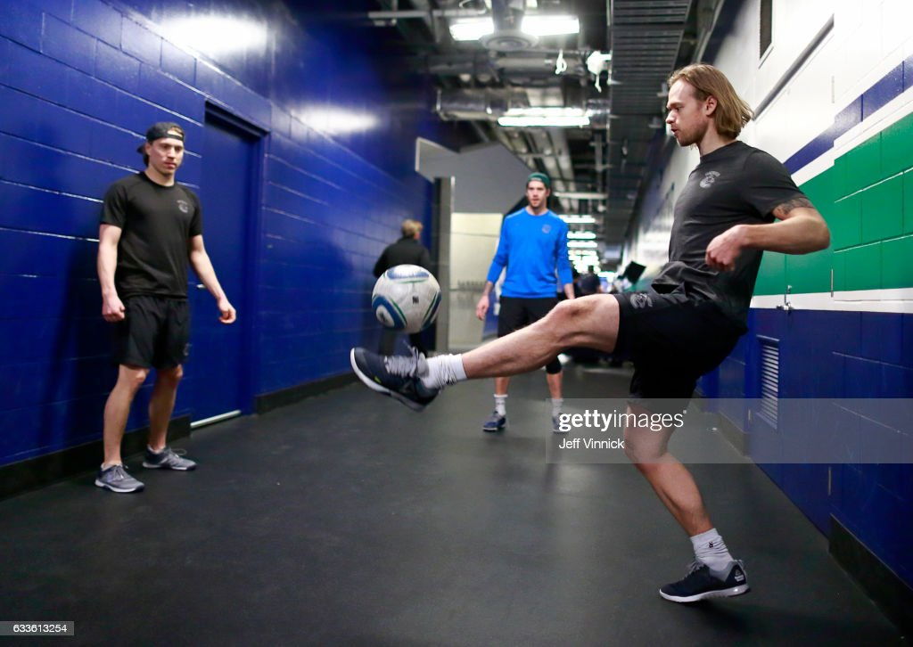 Philip Larsen #63 of the Vancouver Canucks kicks the soccer ball as he warms with teammates Jacob Markstrom #25 and Markus Granlund #60 before their NHL game against the San Jose Sharks at Rogers Arena February 2, 2017 in Vancouver, British Columbia, Canada.