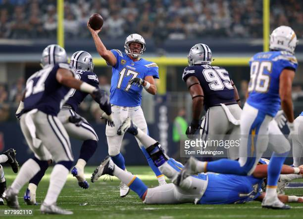 Philip Rivers of the Los Angeles Chargers passes under pressure from DeMarcus Lawrence of the Dallas Cowboys and David Irving of the Dallas Cowboys...