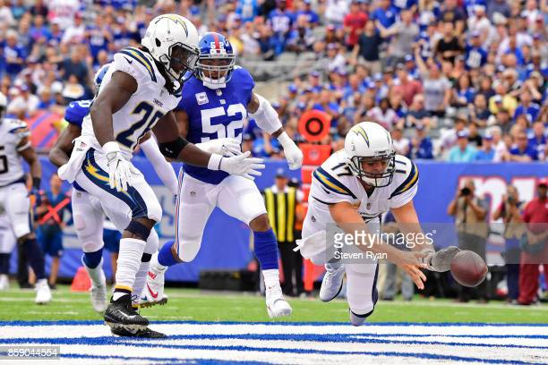 Philip Rivers of the Los Angeles Chargers throws the ball out of the endzone for a safety after a muffed snap under pressure from Jonathan Casillas...