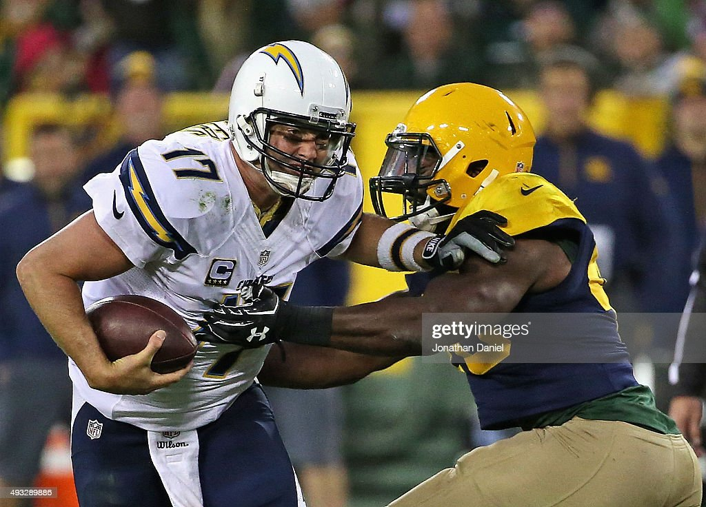 Philip Rivers of the San Diego Chargers gets away from Joe Thomas of the Green Bay Packers at Lambeau Field on October 18 2015 in Green Bay Wisconsin...