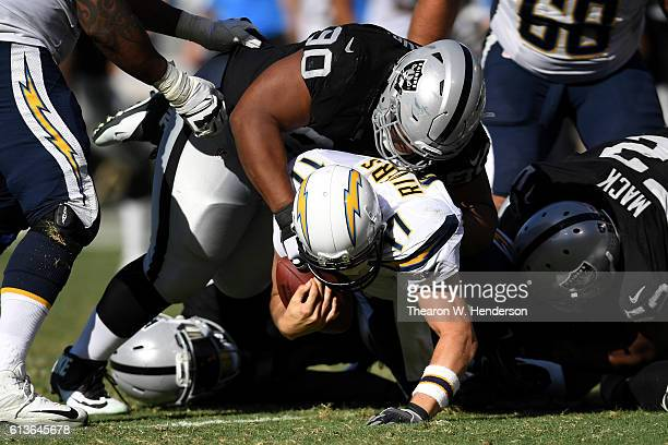 Philip Rivers of the San Diego Chargers is sacked Dan Williams of the Oakland Raiders during their NFL game at OaklandAlameda County Coliseum on...
