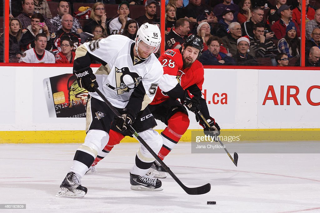 Philip Samuelsson of the Pittsburgh Penguins skates with the puck against Matt Kassian of the Ottawa Senators during an NHL game at Canadian Tire...