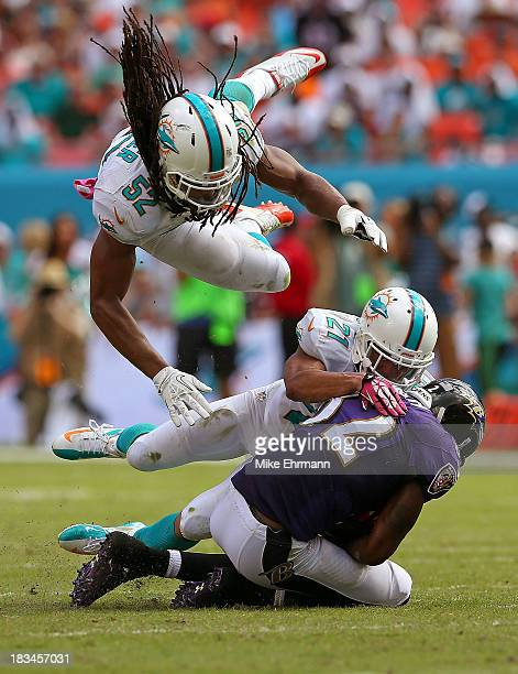 Philip Wheeler of the Miami Dolphins flies over Brent Grimes as he tackles Torrey Smith of the Baltimore Ravens during a game at Sun Life Stadium on...