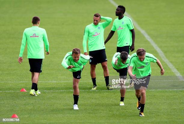 Philipp Bargfrede and Fin Bartels streches during a Werder Bremen training session at Weserstadion on July 2 2017 in Bremen Germany