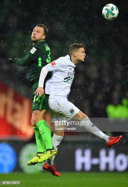 Philipp Bargfrede of Bremen is challenged by Sebastian Maier of Hannover during the Bundesliga match between SV Werder Bremen and Hannover 96 at...