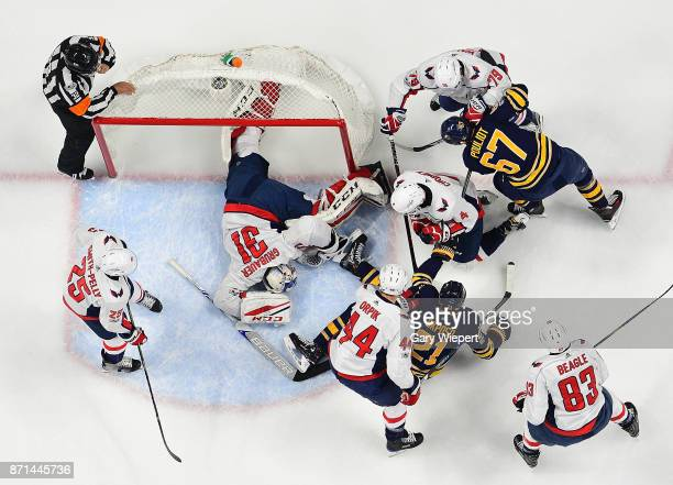 Philipp Grubauer of the Washington Capitals covers up a loose puck as players swarm around the net during an NHL game against the Buffalo Sabres on...