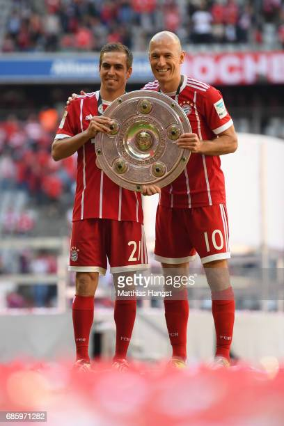 Philipp Lahm and Arjen Robben of Bayern Muenchen pose with the Championship trophy in celebration of the 67th German Championship title following the...
