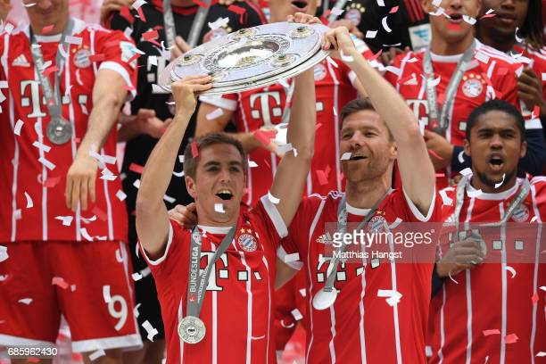 Philipp Lahm and Xabi Alonso of Bayern Muenchen lifts the Championship trophy in celebration of the 67th German Championship title following the...