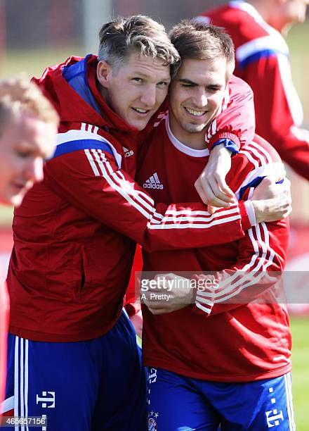 Philipp Lahm is welcomed back to training by Bastian Schweinsteiger of FC Bayern Muenchen during training on March 9 2015 in Munich Germany