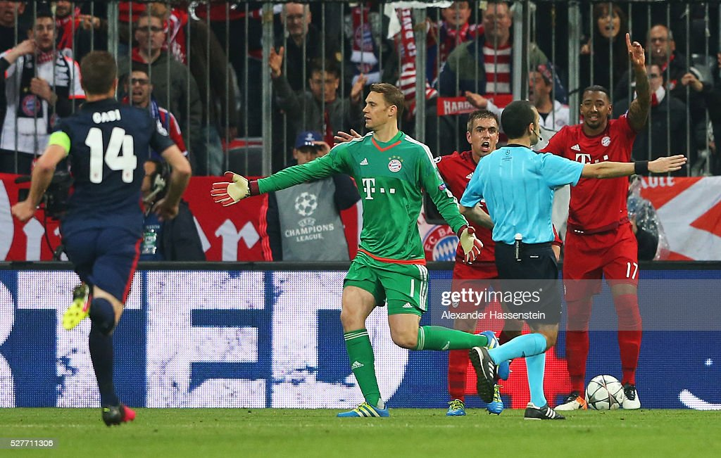 Philipp Lahm (3R), Jerome Boateng (R) and Manuel Neuer of Bayern Munich (2L) react as referee Cuneyt Cakir awards Atletico Madrid a penalty kick during UEFA Champions League semi final second leg match between FC Bayern Muenchen and Club Atletico de Madrid at Allianz Arena on May 3, 2016 in Munich, Germany.