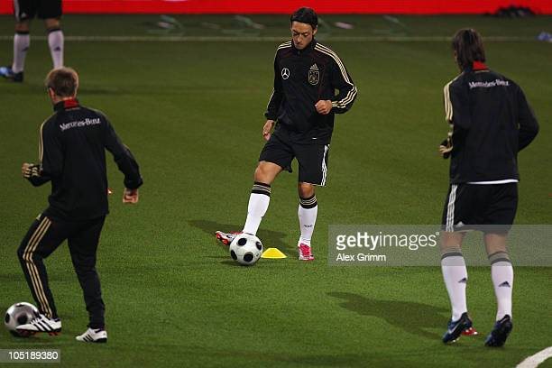 Philipp Lahm Mesut Oezil and Sami Khedira warm up during a training session of the German national football team at the Astana Arena on October 11...