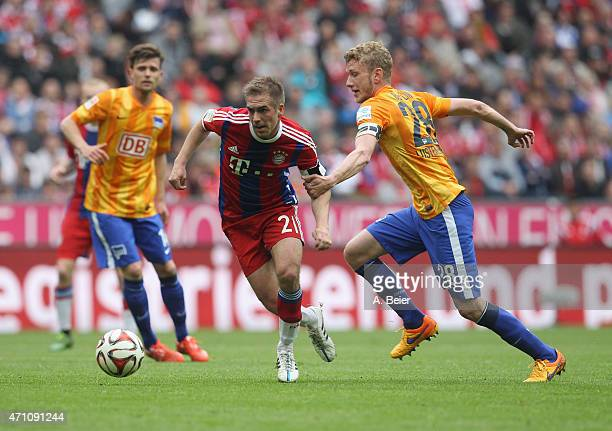 Philipp Lahm of Bayern Muenchen fights for the ball with Fabian Lustenberger of Hertha BSC during the Bundesliga match between FC Bayern Muenchen and...