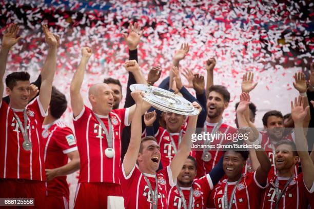 Philipp Lahm of Bayern Muenchen lifts the championship trophy during an awarding ceremony after the Bundesliga match between Bayern Muenchen and SC...