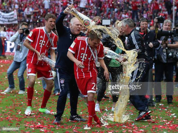 Philipp Lahm of Bayern Muenchen receives a beer shower from Bayern assistant coach Hermann Gerland following the Bundesliga match between Bayern...