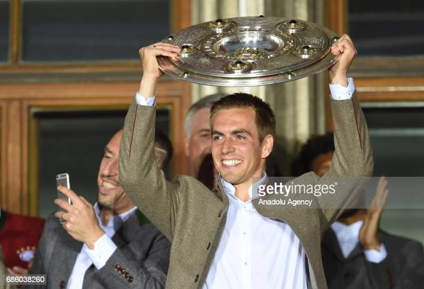 Philipp Lahm of Bayern Munich celebrates winning the German soccer championship with the trophy on a balcony of the town hall in Munich Germany on...